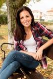 Mujer joven hermosa que se sienta en parque en la caída Imagen de archivo libre de regalías