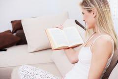 Mujer joven hermosa que se sienta en pijamas y que lee un libro fotos de archivo