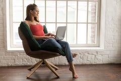 Mujer joven hermosa que se sienta en silla cómoda y que usa el ordenador portátil imagen de archivo
