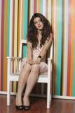 Mujer joven hermosa que se sienta en silla contra la pared rayada colorida Foto de archivo
