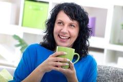 Mujer joven hermosa que se sienta en su coffe de consumición casero, sonriendo Imagen de archivo libre de regalías