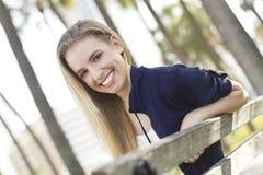 Mujer joven hermosa que se sienta en un banco Fotos de archivo libres de regalías