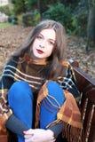 Mujer joven hermosa que se sienta en un banco en un parque Imagenes de archivo