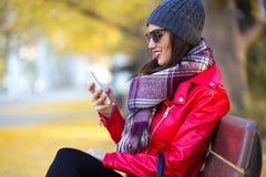 Mujer joven hermosa que se sienta en un banco y que usa su teléfono móvil en otoño Foto de archivo