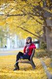 Mujer joven hermosa que se sienta en un banco y que usa su teléfono móvil en otoño Fotografía de archivo