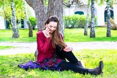 Mujer joven hermosa que se sienta en un césped verde y que habla en el teléfono celular Fotografía de archivo