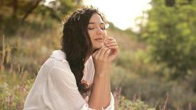 Mujer joven hermosa que se sienta en un campo de trigo en la puesta del sol del verano Concepto de la belleza y del verano metrajes