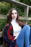 Mujer joven hermosa que se sienta en un puente de madera Fotografía de archivo