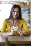 Mujer joven hermosa que se sienta en un té de la cafetería y de la bebida Imagen de archivo