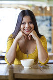 Mujer joven hermosa que se sienta en un té de la cafetería y de la bebida Fotos de archivo