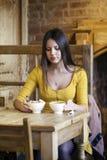 Mujer joven hermosa que se sienta en un té de la cafetería y de la bebida Foto de archivo