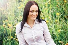 Mujer joven hermosa que se sienta en una hierba Foto de archivo