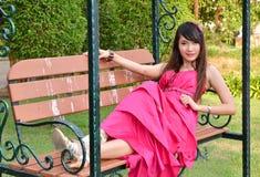 Mujer joven hermosa que se sienta en una silla Imágenes de archivo libres de regalías