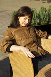 Mujer joven hermosa que se sienta en una silla de mimbre Fotos de archivo