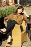 Mujer joven hermosa que se sienta en una silla de mimbre Imagen de archivo libre de regalías