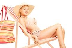 Mujer joven hermosa que se sienta en una silla de playa Imágenes de archivo libres de regalías