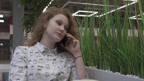 Mujer joven hermosa que se sienta en una tabla en un café, hablando en el teléfono metrajes