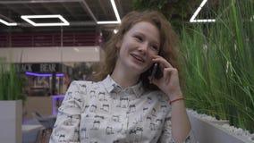 Mujer joven hermosa que se sienta en una tabla en un café, hablando en el teléfono almacen de metraje de vídeo