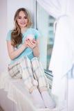 Mujer joven hermosa que se sienta por la ventana con la taza de té Fotografía de archivo