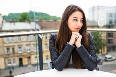 Mujer joven hermosa que se sienta solamente en café en una espera de la terraza para la orden Descanso para tomar café después de foto de archivo
