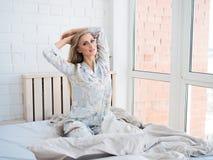 Mujer joven hermosa que se sienta y que estira en cama por la mañana Foto de archivo
