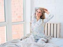 Mujer joven hermosa que se sienta y que estira en cama por la mañana Fotos de archivo libres de regalías