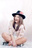 Mujer joven hermosa que se sienta y que sonríe feliz Imagen de archivo