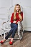 Mujer joven hermosa que sienta en los zapatos de moda Piernas en tacón alto rojo Imagenes de archivo