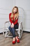 Mujer joven hermosa que sienta en los zapatos de moda Piernas en tacón alto rojo Imagen de archivo libre de regalías