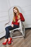 Mujer joven hermosa que sienta en los zapatos de moda Piernas en tacón alto rojo Fotografía de archivo libre de regalías