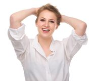 Mujer joven hermosa que sonríe con las manos a la cabeza Imagen de archivo libre de regalías