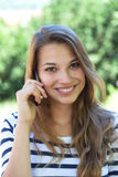 Mujer joven hermosa que sonríe en el teléfono en un parque Fotos de archivo libres de regalías