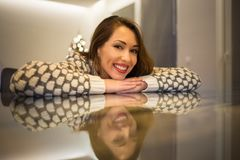 Mujer joven hermosa que sonríe en la cámara mientras que se inclina en una tabla de cristal fotografía de archivo