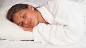 Mujer joven hermosa que sonríe a la cámara mientras que cae dormido imagenes de archivo