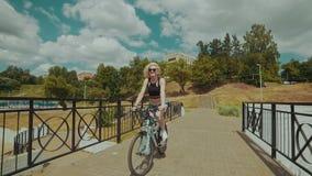 Mujer joven hermosa que sonríe mientras que monta su bicicleta en día de verano soleado metrajes