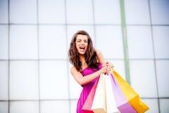 Mujer joven hermosa que sostiene bolsos de compras Imagen de archivo libre de regalías