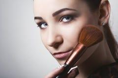 Mujer joven hermosa que sostiene diversos cepillos del maquillaje imagenes de archivo