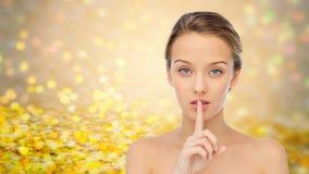 Mujer joven hermosa que sostiene el finger en los labios Fotos de archivo libres de regalías
