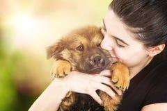 Mujer joven hermosa que sostiene el perrito lindo al aire libre Foto de archivo libre de regalías