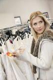 Mujer joven hermosa que sostiene el precio mientras que mira lejos en tienda nupcial Fotografía de archivo libre de regalías