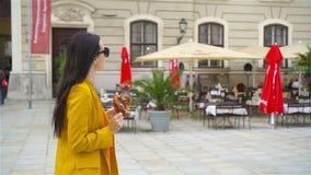 Mujer joven hermosa que sostiene el pretzel y que se relaja en parque almacen de video