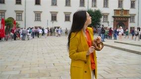 Mujer joven hermosa que sostiene el pretzel y que se relaja en parque almacen de metraje de vídeo