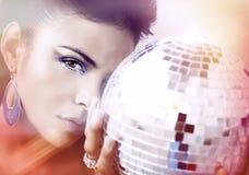 Mujer joven hermosa que sostiene la bola de discoteca Imagenes de archivo