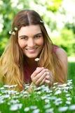 Mujer joven hermosa que sostiene la flor en el parque fotos de archivo