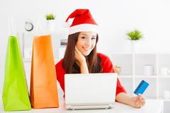 Mujer joven hermosa que sostiene la tarjeta de crédito con la computadora portátil Navidad Imagen de archivo libre de regalías