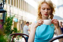 Mujer joven hermosa que sostiene la taza de café que se sienta en restaurante Fotos de archivo