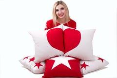 Mujer joven hermosa que sostiene una almohada con el corazón Almohadas hermosas para adornar el interior de la casa Almohada con  Fotos de archivo