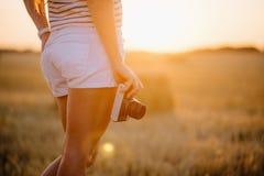 Mujer joven hermosa que sostiene una cámara del vintage en el nivel de la cadera Foto de archivo