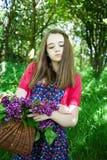 Mujer joven hermosa que sostiene una cesta de flores Fotografía de archivo libre de regalías