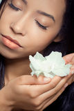 Mujer joven hermosa que sostiene una flor blanca Fotos de archivo libres de regalías